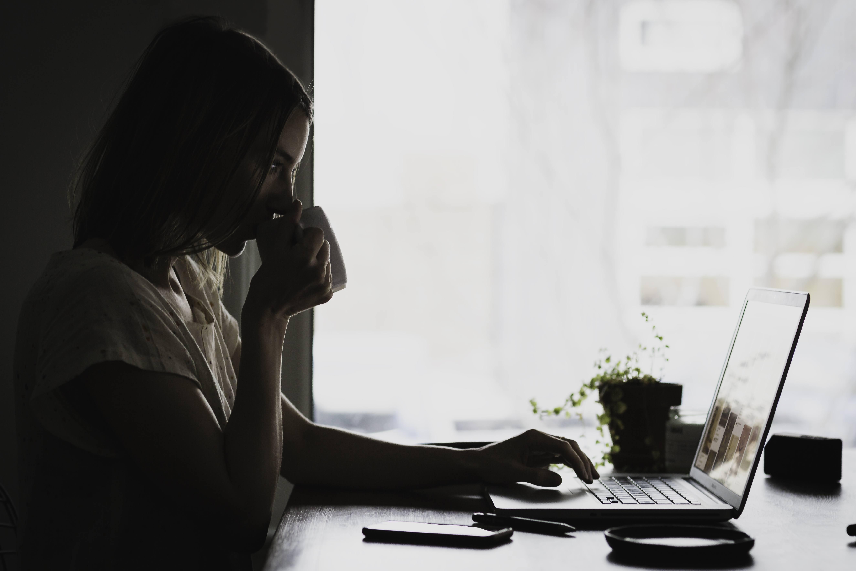 Vrouw met kop thee achter de laptop werkplek