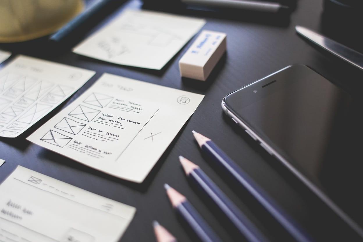 Papiertjes met aantekeningen, potloden en smartphone