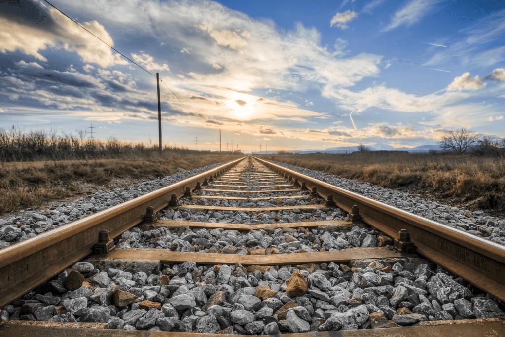 Foto van treinrails in de natuur met mooie lucht